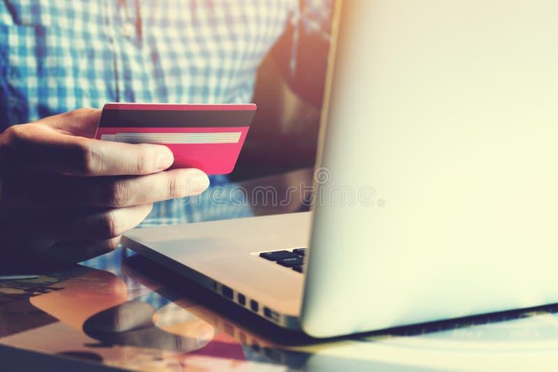 Jeune homme asiatique tenant la carte de crédit avec utiliser l'ordinateur portable et en ligne photo stock