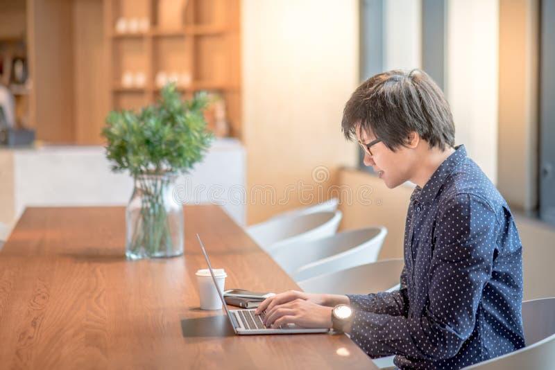 Jeune homme asiatique travaillant avec l'ordinateur portable dans le bureau image libre de droits