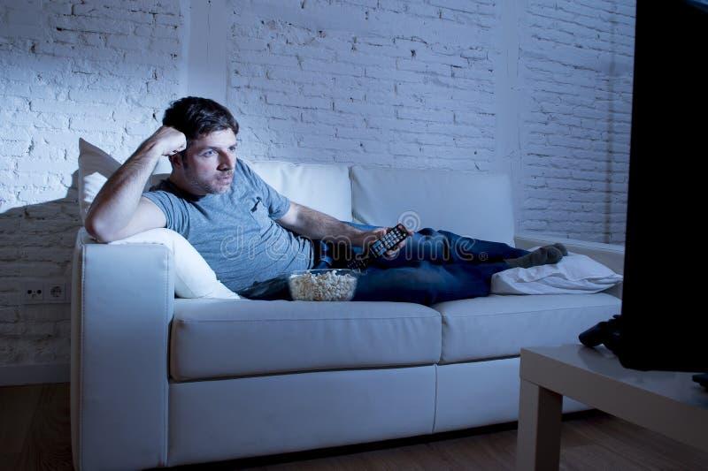 Jeune homme attirant à la maison se trouvant sur le divan au salon regardant la TV juger à télécommande photographie stock libre de droits