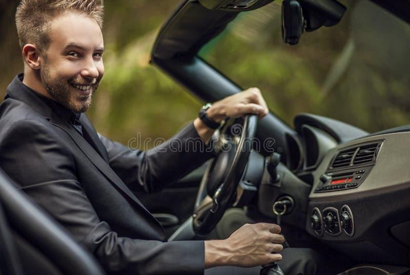 Jeune homme attirant élégant dans la voiture convertible extérieure. image stock