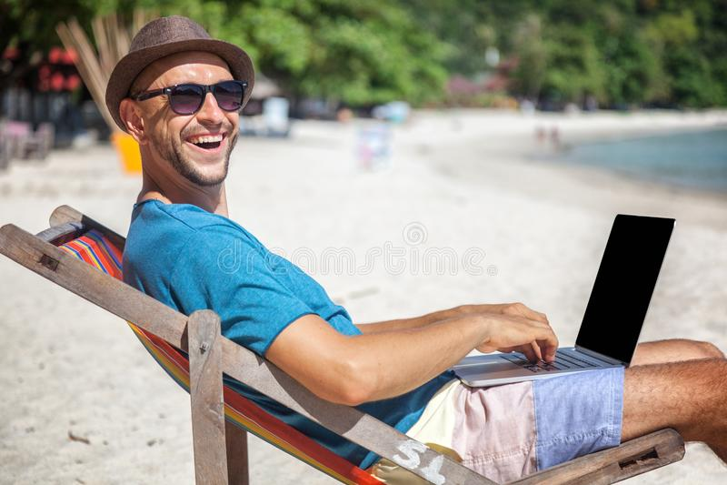 Jeune homme attirant avec l'ordinateur portable travaillant à la plage Liberté, image libre de droits
