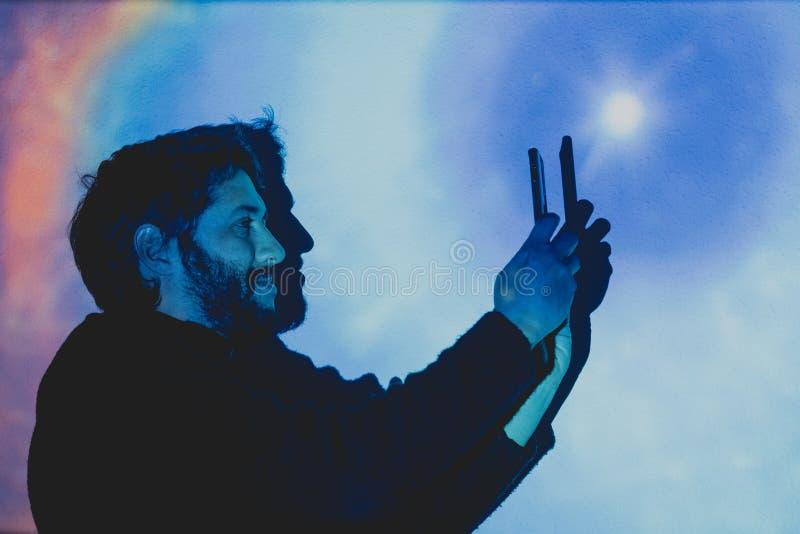 Jeune homme attirant avec la barbe prenant des photos dans un environnement futuriste images libres de droits