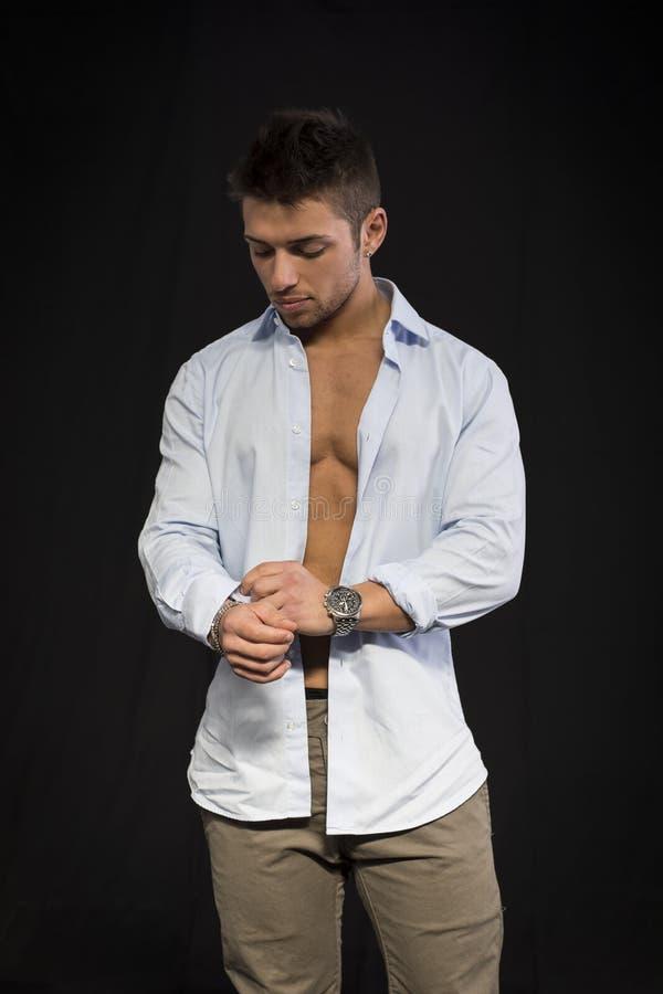 Jeune homme attirant avec la chemise ouverte sur le torse musculaire photo libre de droits
