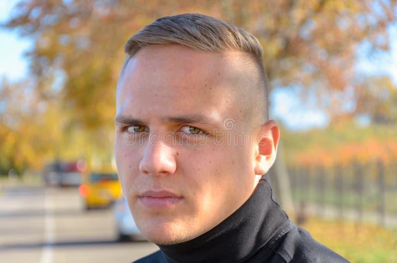 Jeune homme attirant avec la coupe de cheveux moderne à la mode photo libre de droits