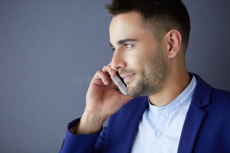 Jeune homme attirant avec le smartphone sur le fond de couleur photographie stock libre de droits