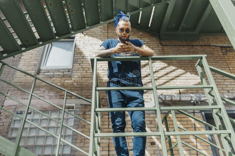 Jeune homme attirant avec les dreadlocks bleus se tenant à l'escalier photos stock