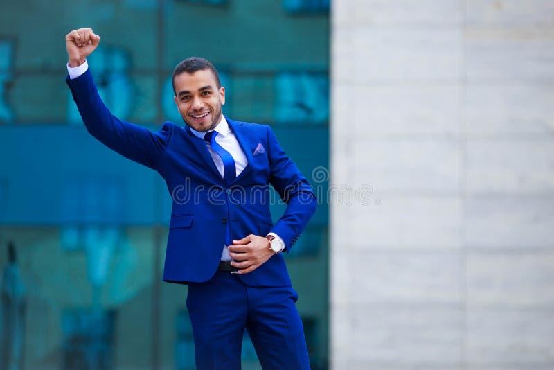 Jeune homme attirant d'affaires dans le costume célébrant le succès dessus  photographie stock libre de droits