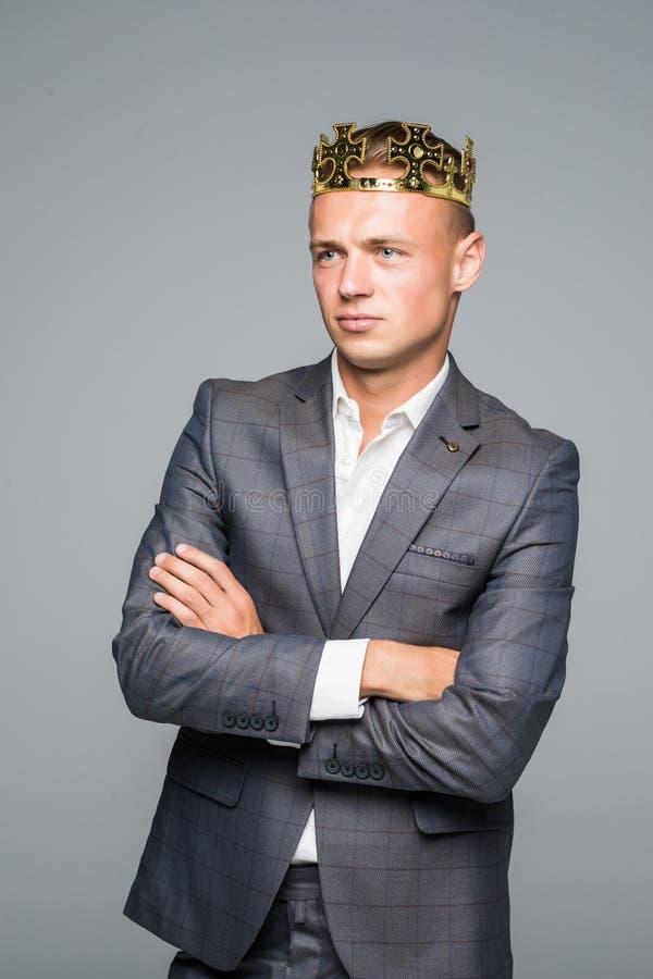Jeune homme attirant dans le costume tenant au-dessus du sien la tête une couronne d'or sur un fond gris photo stock