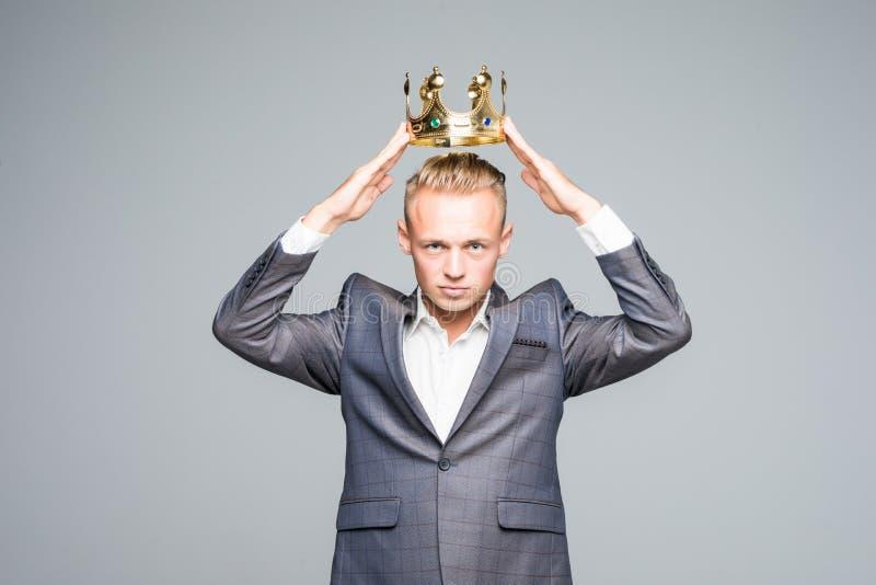 Jeune homme attirant dans un costume gris tenant au-dessus du sien la tête une couronne d'or sur un fond gris images libres de droits