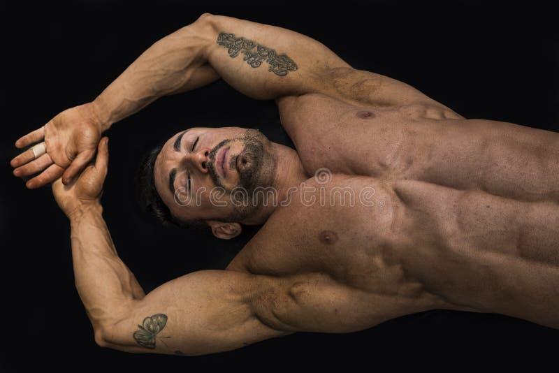 Jeune homme attirant de muscle s'étendant sur le plancher images stock