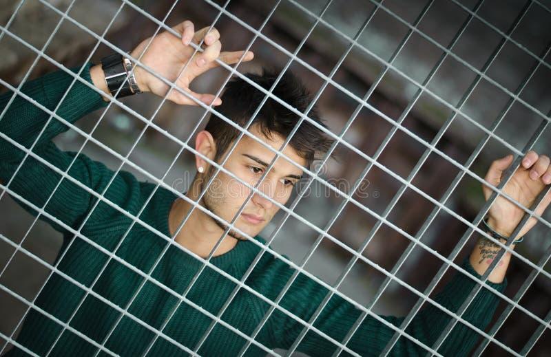 Jeune homme attirant derrière le réseau en métal ou d'acier image stock