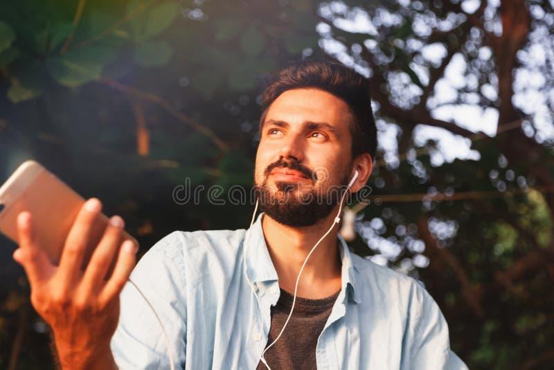 Jeune homme attirant du Latino de type de métis avec une barbe écoutant la musique sur des écouteurs, dehors photo libre de droits