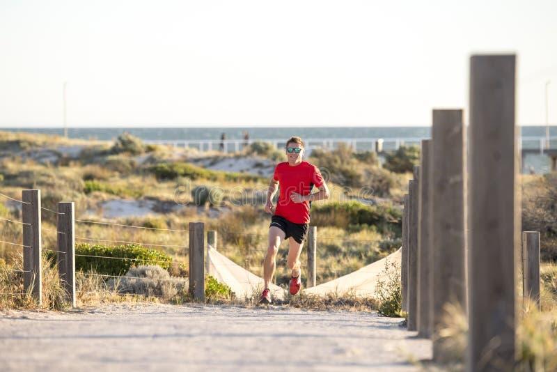 Jeune homme attirant et heureux de coureur de sport avec l'ajustement et la formation saine forte de corps sur outre de la voie d image libre de droits