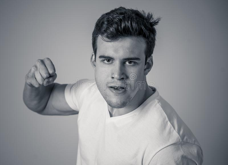 Jeune homme attirant fâché et furieux dans la position de boxe prête à combattre photographie stock