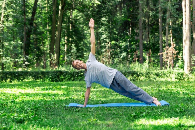 Jeune homme attirant faisant le yoga en parc : planche de posture photo libre de droits