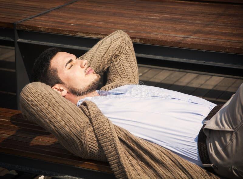 Jeune homme attirant fixant sur le banc en bois images stock