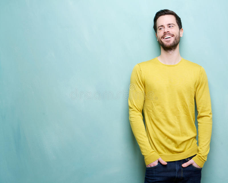 Jeune homme attirant riant sur le fond bleu photo stock