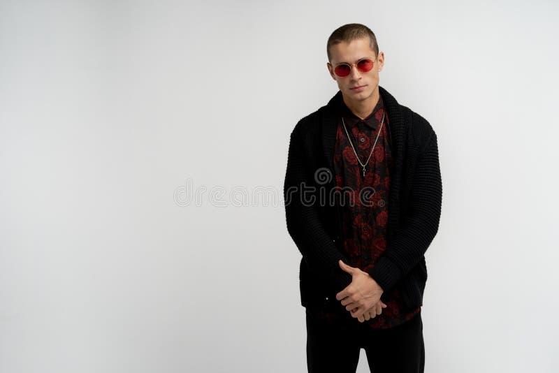 Jeune homme attirant s?r s?rieux avec la coupe de cheveux courte dans des lunettes de soleil rouges utilisant le chandail et la c image libre de droits