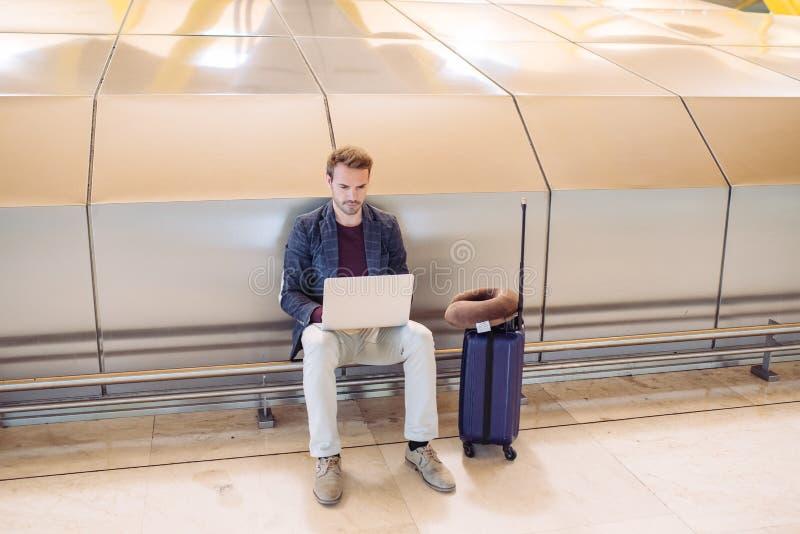 Jeune homme attirant s'asseyant à l'aéroport fonctionnant avec un lapto photographie stock