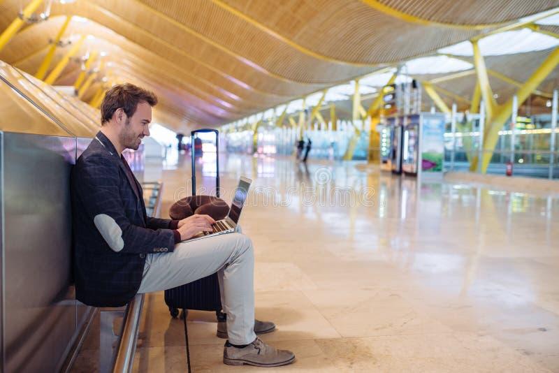 Jeune homme attirant s'asseyant à l'aéroport fonctionnant avec un lapto images stock