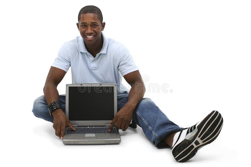 Jeune homme attirant s'asseyant sur l'étage avec l'ordinateur portable photo libre de droits
