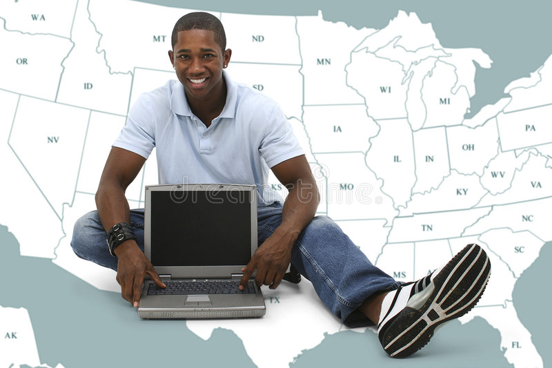 Jeune homme attirant s'asseyant sur l'étage avec l'ordinateur portable image libre de droits