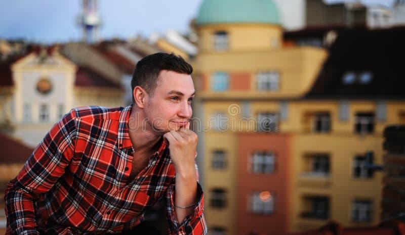 Jeune homme attirant s'asseyant sur le toit semblant parti et le sourire Ville de fond images stock