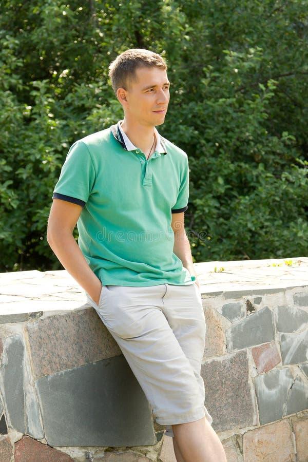 Jeune homme attirant semblant latéral et se penchant contre un parapet en pierre images stock