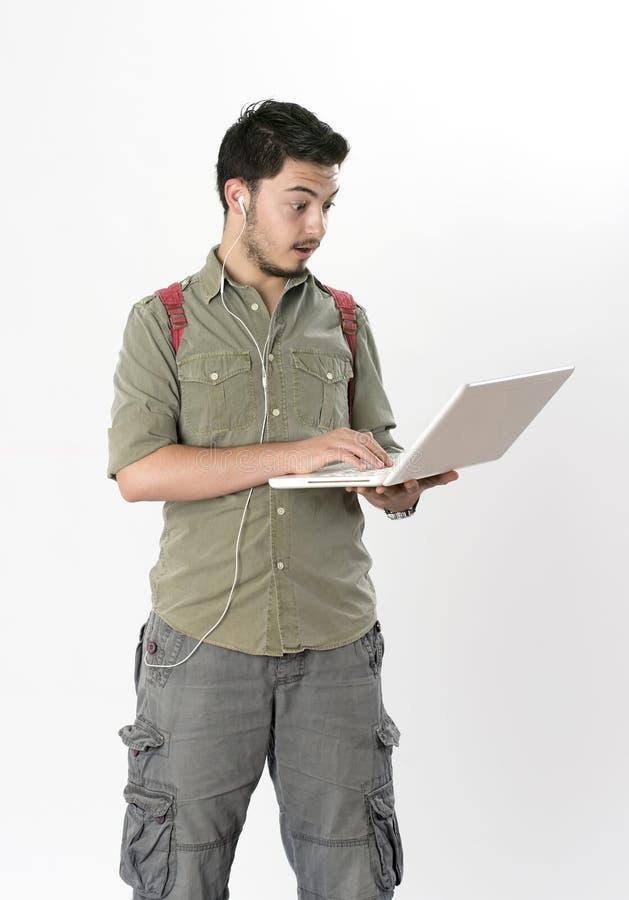 Jeune homme attirant travaillant sur l'ordinateur portable photographie stock libre de droits
