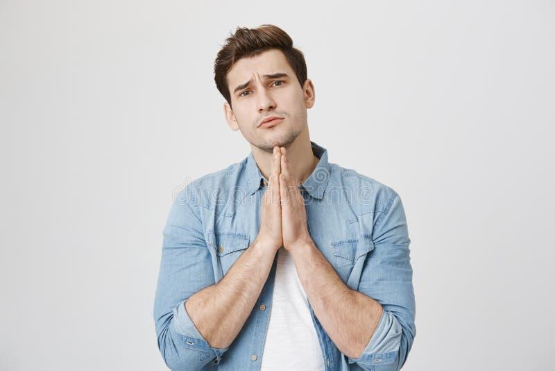 Jeune homme attirant, unshaved mignons, avec prier l'expression et le geste, regardant sincèrement l'appareil-photo, d'isolement  photographie stock