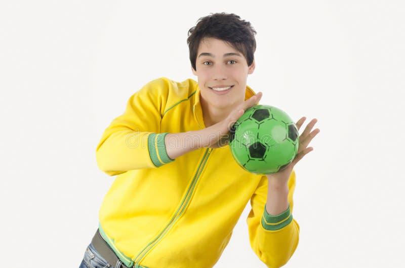 Jeune homme attrapant une boule du football image stock