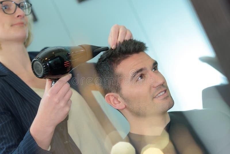 Jeune homme au coiffeur photographie stock libre de droits