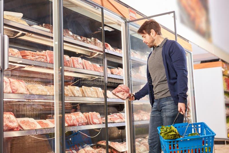 Jeune homme au congélateur achetant de la viande photos libres de droits