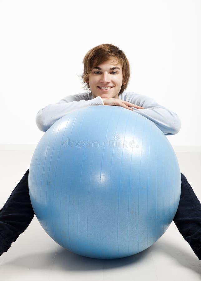 Jeune homme au-dessus d'une boule de pilates photos libres de droits