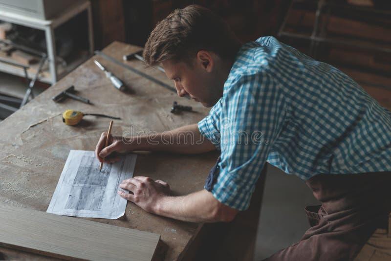 Jeune homme au travail en menuiserie photographie stock libre de droits