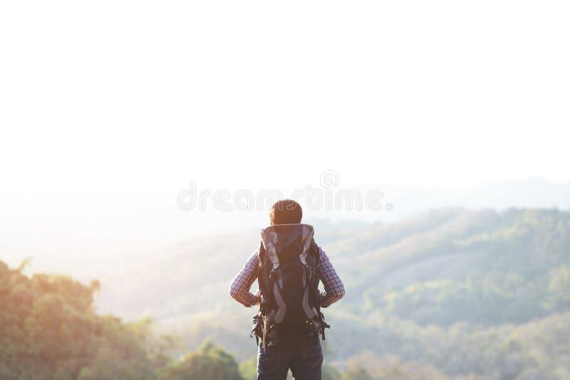 Jeune homme augmentant la position de d?placement sur la falaise dans le mode de vie de voyage d'?t? photos stock