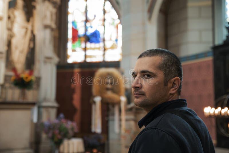 Jeune homme aux cheveux noirs dans d'une église catholique des vues avec enthousiasme image stock