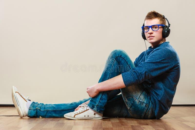 Jeune homme avec des écouteurs se reposant sur le plancher photo stock