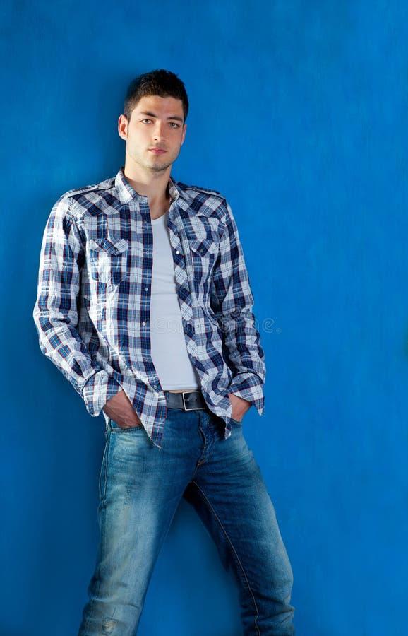 Jeune homme avec des jeans de denim de chemise de plaid dans le bleu photographie stock libre de droits