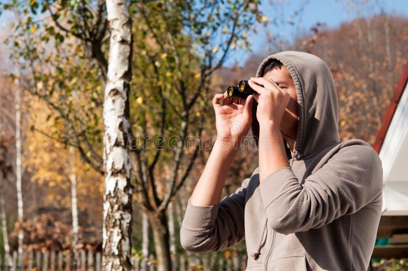 Jeune homme avec des jumelles observant la nature photos libres de droits