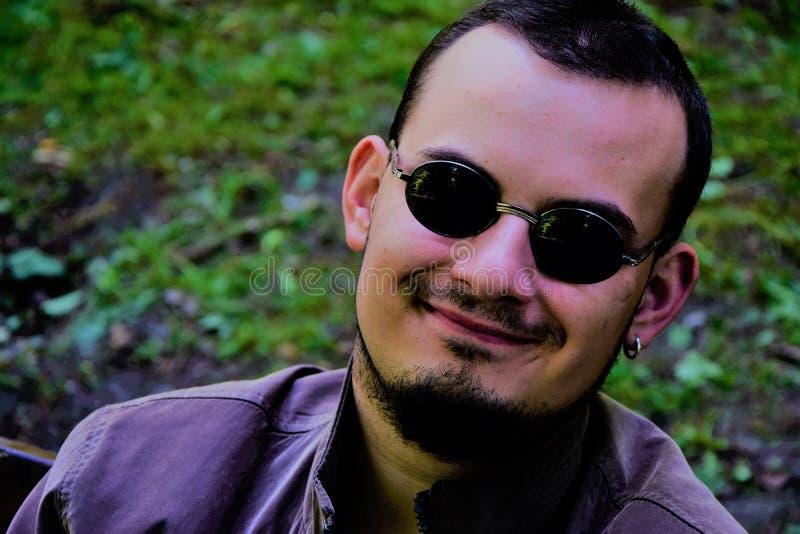 Jeune homme avec des lunettes de soleil et le sourire fou image stock