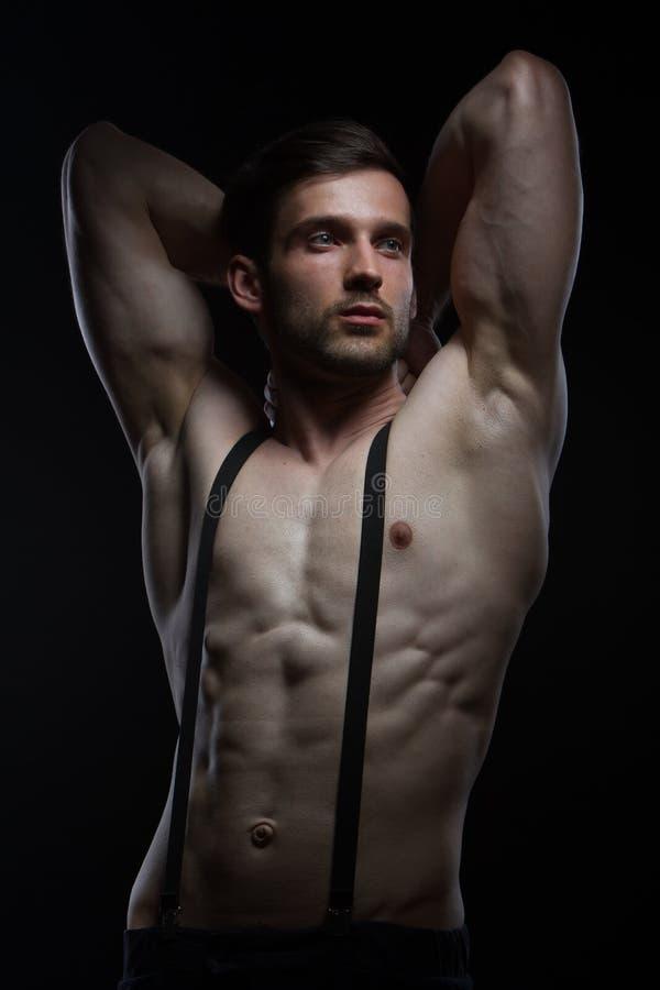 Jeune homme avec des muscles avec des accolades sur le pantalon sur le fond noir image stock