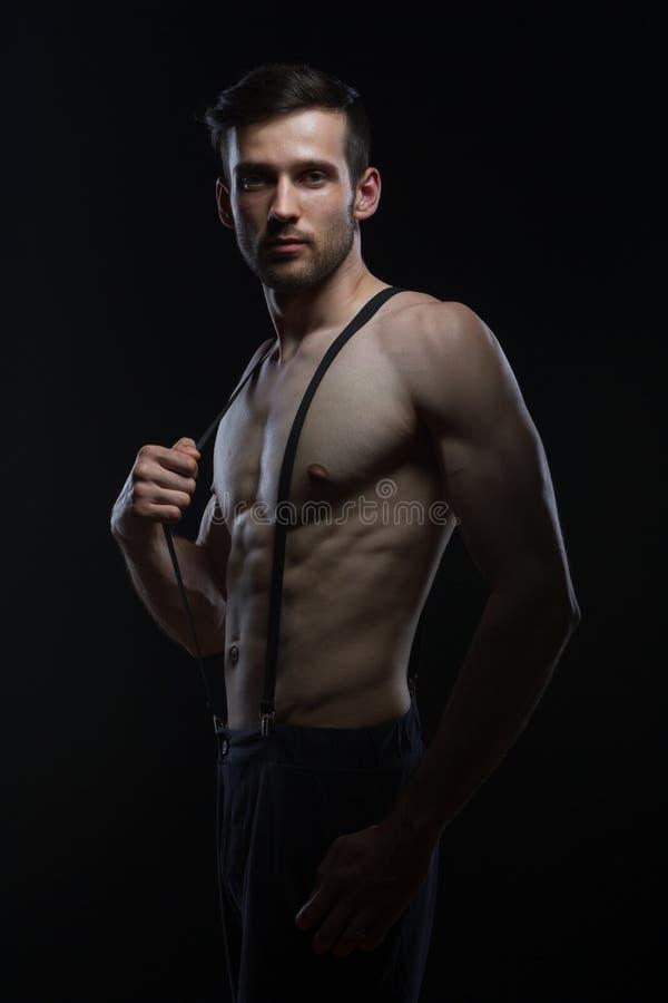 Jeune homme avec des muscles avec des accolades sur le pantalon sur le fond noir images stock