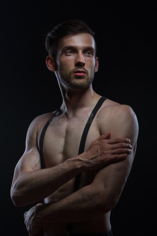 Jeune homme avec des muscles avec des accolades sur le pantalon sur le fond noir photographie stock