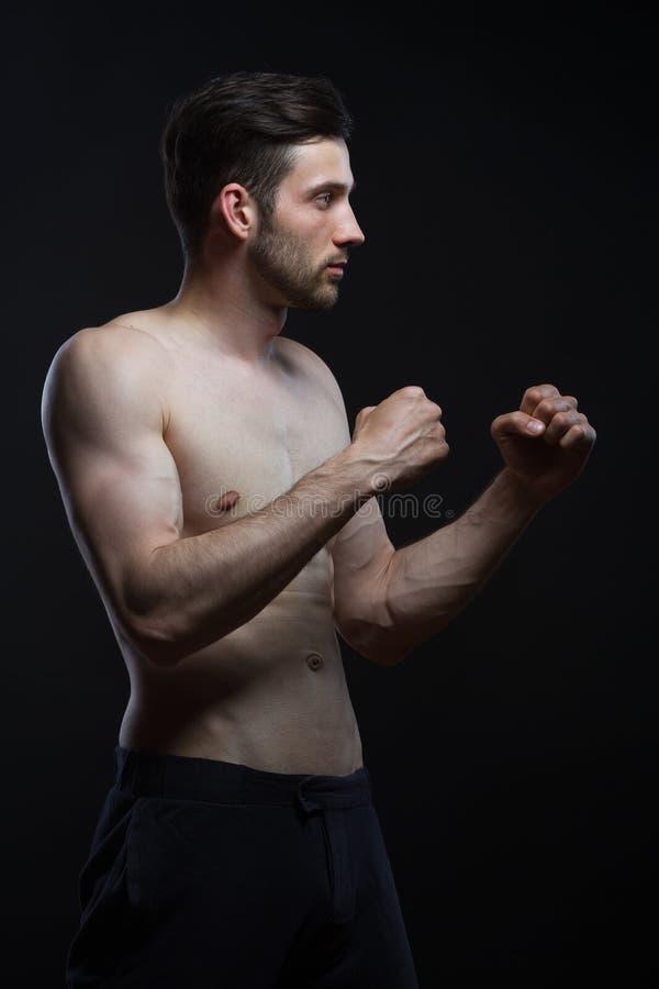 Jeune homme avec des muscles enfermant dans une boîte sur le fond noir image stock