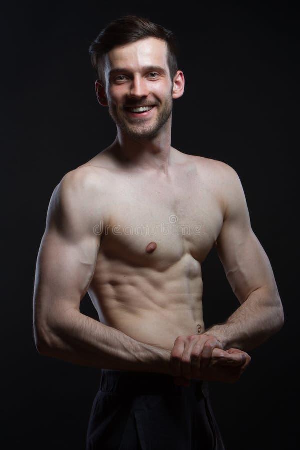 Jeune homme avec des muscles regardant sur l'appareil-photo souriant sur le fond noir image libre de droits