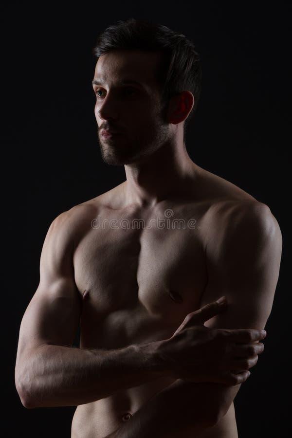 Jeune homme avec des muscles sur le fond noir photo stock