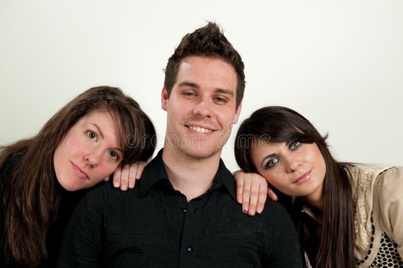 Jeune homme avec deux femmes images stock