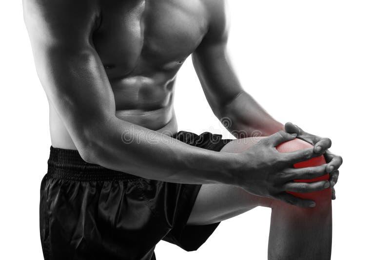 Jeune homme avec douleur de genou, d'isolement sur le fond blanc, monochrom images stock