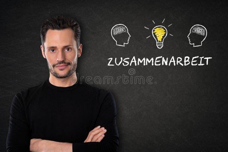 Jeune homme avec et x27 ; Zusammenarbeit& x27 ; texte, tête avec des cerveaux et ampoule-idée légère sur un fond de tableau noir  photographie stock